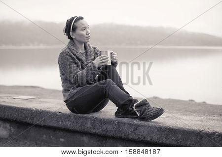 B&W of woman relaxing by lake with her coffee.