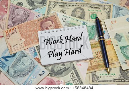 Notebook page with text WORK HARD, PLAY HARD, background from different world Currencies