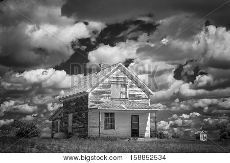 horizontal black and white image of an old abandoned white house  with a veranda and peeling paint in a rural countryside under a dramatic cloudy sky in summertime.