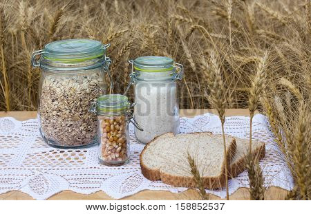 horizontal image of three jars full of rolled oats and popcorn seeds and wholewheat flour with a slice of bread lying on a table sitting in the wheat field