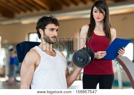 Female personal trainer looking at an athlete doing an exercise