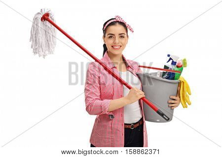 Happy young woman holding a mop and a bucket filled with cleaning products isolated on white background