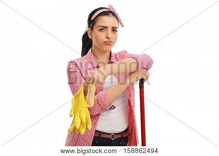 Tired young woman with a pair of cleaning gloves and a mop isolated on white background