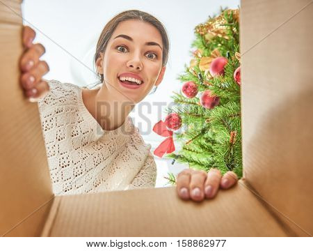 Merry Christmas and Happy Holidays! Cheerful pretty young woman opening a Christmas present. Girl having fun near Christmas tree indoors. View from inside of the box.