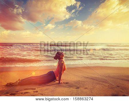 Vintage retro hipster style image of Yoga outdoors on beach - woman practices Ashtanga Vinyasa yoga Surya Namaskar Sun Salutation asana Urdhva Mukha Svanasana - upward facing dog pose on sunset