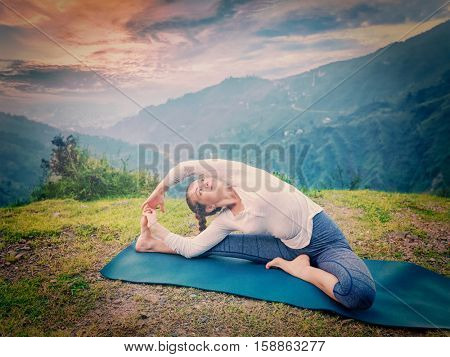 Yoga outdoors - young sporty fit woman doing Hatha Yoga asana parivritta janu sirsasana - Revolved Head-to-Knee Pose - in. Vintage retro effect filtered hipster style image.