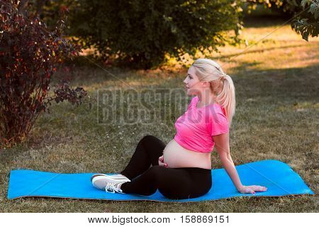 Side view on pregnant sitting in lotus pose. Expectant woman with naked belly practicing yoga at nature, meditation, relaxation, healthy pregnancy concept