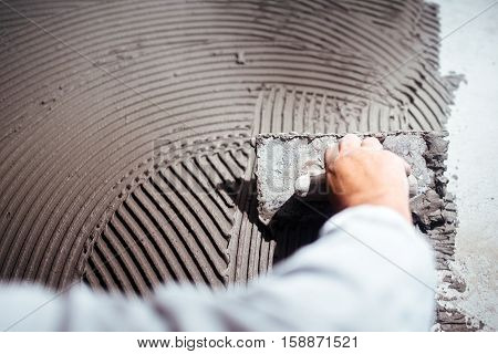 Industrial Close Up Of Worker Hand Adding Adhesive For Ceramic Tiles Installation