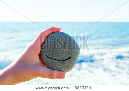 Kid's hand holding a stone with smiling face next to the sea in a sunny day