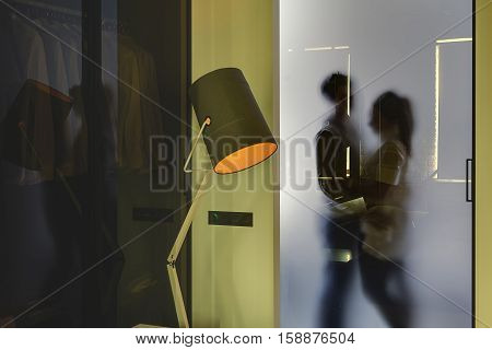 Silhouette of the hugging couple which is behind the frosted glassy door in the glowing modern interior with yellow walls. In front of the door there is a luminous lamp with an orange lampshade.