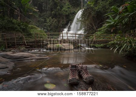Motion blurred water of Pa Dok Siew Waterfall (Rak Jung waterfall )with trekking shoes as a foreground beautiful waterfall in deep forest Doi Inthanon national park. Rainy season Chiangmai , Thailand