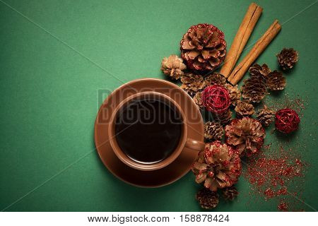 Top view on cup of coffee with cinnamon and pinecone on the green paper background