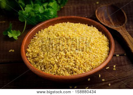 Raw bulgur, wheat grains in bowl on wooden table. Close up view