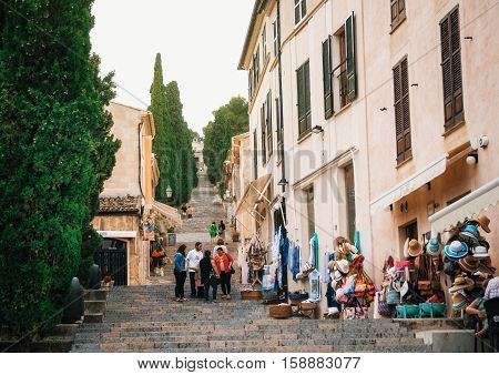 Pollensa Mallorca Spain - May 24 2015: Stores and souvenir shops with the tourists the seller and the buyer on the steps of the stairway Via Crusis to the Calvary church from the center of Pollensa Mallorca.