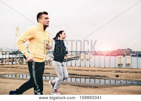 Couple of young people in sportswear running on the bridge. Living healthy