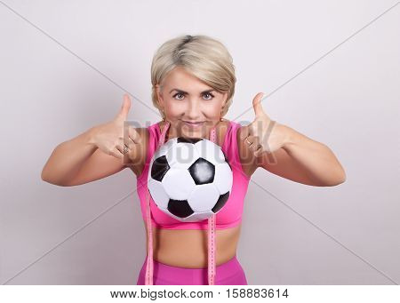 Athlete holding soccer ball with your chin and hands shows sign perfectly