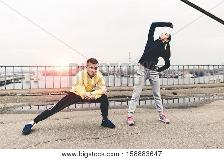 Couple young athletes in sportswear are training on a city bridge