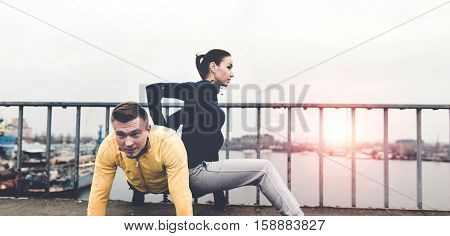Couple young athletes in sportswear are training on a city bridge on the Sunset