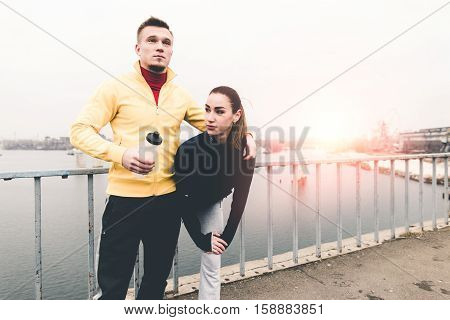 Couple young athletes in sports clothing standing on a city bridge on the sunset