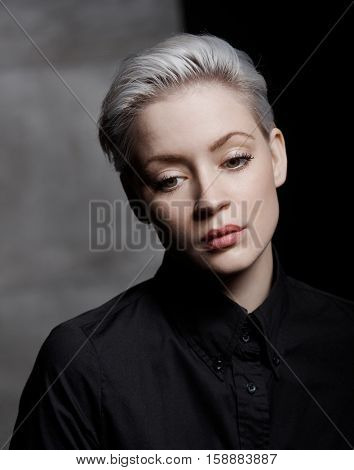 Portrait of sad woman with short hair looking down.