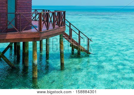 Part of bungalow with stair descending into the sea. Turquoise color of the lagoon. Tropical island in the Indian Ocean. Luxury holiday.