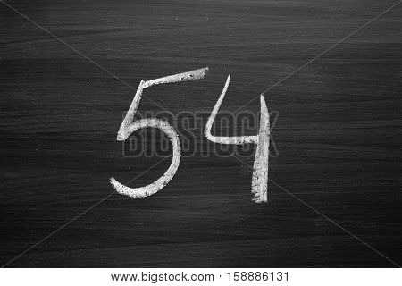 number fifty four enumeration written with a chalk on the blackboard