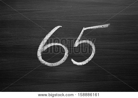 number sixty five enumeration written with a chalk on the blackboard