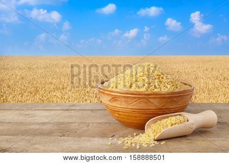 Bulgur or couscous in bowl. wheat grains in sack. Bulgur in ceramic bowl on table with field of wheat on the background. Agriculture and harvest concept. Gold wheat field and blue sky