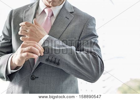 Midsection of mature businessman buttoning sleeve