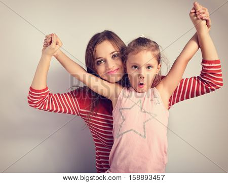 Playful Mother And Crazy Joking Grimacing Kid Holding Each Other By The Hands. Toned Vintage Closeup