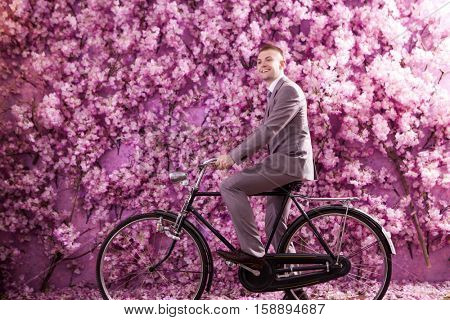 Side view of smiling bridegroom riding bicycle against wall covered with pink flowers