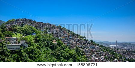 View from Mirante Dona Marta located in Tijuca Forest to the hill of the slum, favela Morro dos Prazeres and blue sky in Rio de Janeiro, Brazil