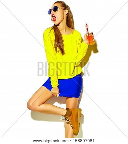 portrait of beautiful crazy smiling brunette woman model in casual hipster summer colorful clothes with red lips isolated on white drinking soda from bottle with straw in sunglasses