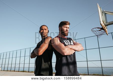 Two young basketball players standing at the playgroud with arms folded