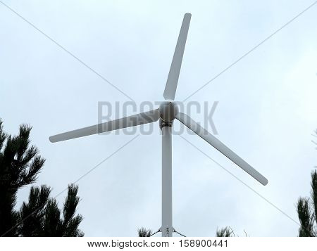 Renewable Energy Concept Wind turbine over blue sky background.