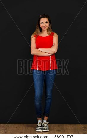 Beautiful woman with hands folded standing in front of a black wall