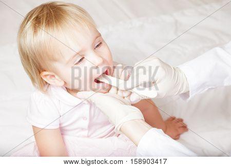 Pediatrician examines sitting child using wooden tongue depressor to check girl's sore throat