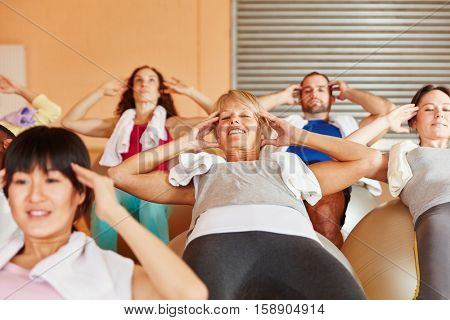 Senior working out at fitness class with people