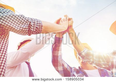 business, building, partnership, gesture and people concept - close up of builders in hardhats making high five outdoors