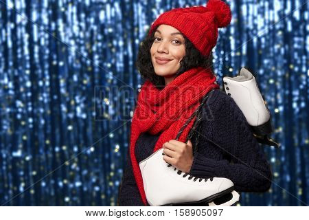 Smiling young woman in red winter hat and scarf carrying a pair of ice skates over blue glittery background