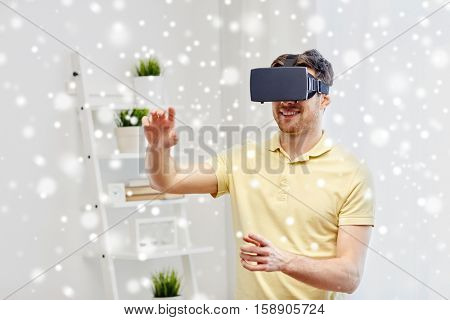 technology, augmented reality, gaming, entertainment and people concept - happy young man with virtual headset or 3d glasses playing video game at home over snow