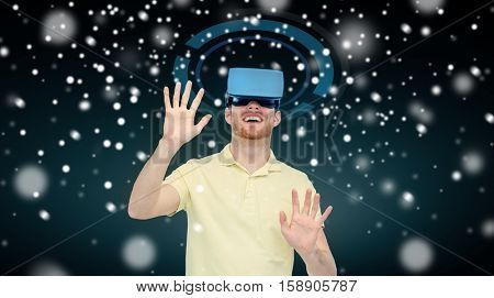 technology, augmented reality, winter, christmas and people concept - happy young man with virtual headset or 3d glasses playing game over black background and snow