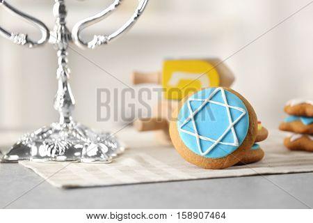 Tasty glazed cookies for Hanukkah on grey table against light background
