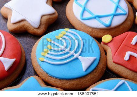 Tasty glazed cookies for Hanukkah on dark background, closeup