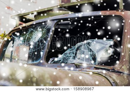 wartime, damage and danger concept - war truck with broken windshield glass over snow