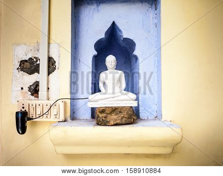 Buddha is plugged to the charger. Meditation charging. Buddha's figurine covers the mobile phone connected to the charger.