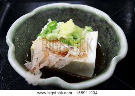Tofu side dish decorated with ginger spring onion and cuttle fish gross in Kyoto