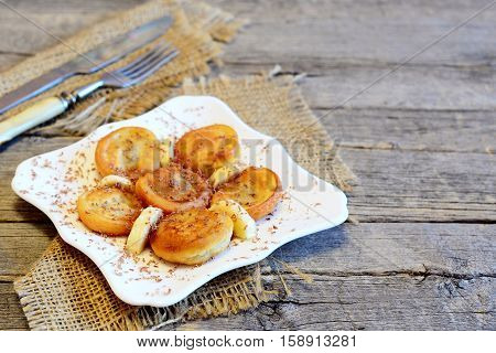Fried bananas in batter on a plate, fork, knife, burlap on wooden background with copy space for text. Vegetarian banana fritters recipe. Vintage style. Closeup
