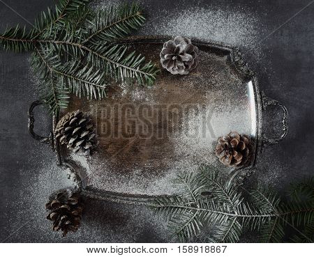 New Year background: pine cones and fir branches on vintage tray. Dark photo