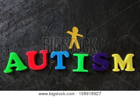 Paper cutout of a child with Autism spelled in play letters